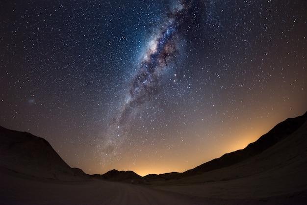Ciel étoilé et arc de la voie lactée, avec des détails de son noyau coloré, remarquablement lumineux, capturés dans le désert du namib en namibie, en afrique. le petit nuage magellanique à gauche. Photo Premium