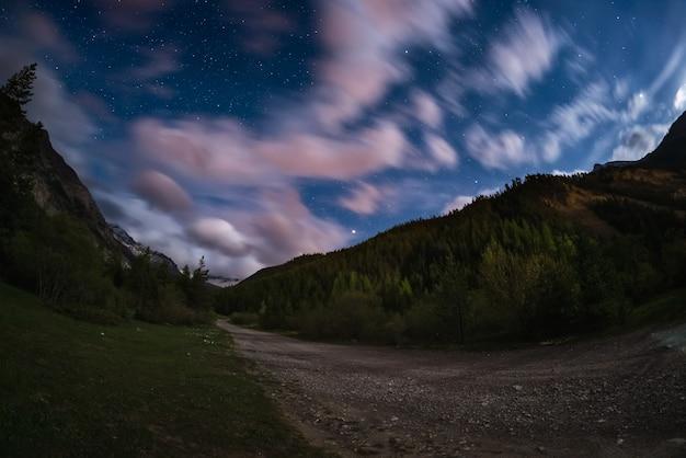 Le ciel étoilé avec nuages colorés de mouvement flou et clair de lune Photo Premium