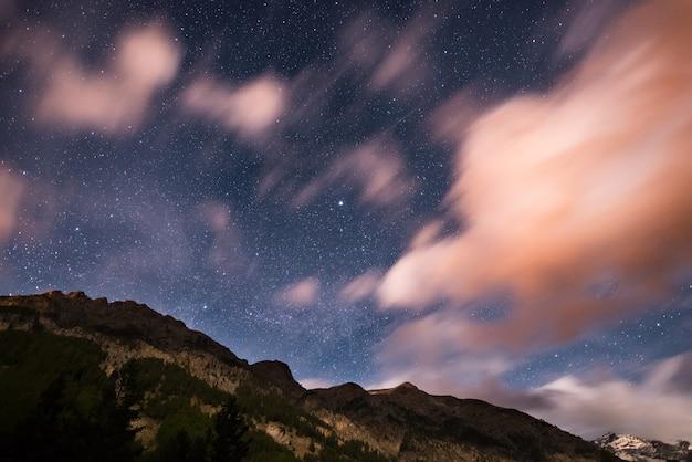 Le ciel étoilé avec des nuages de mouvement flou et clair de lune. alpes européennes Photo Premium