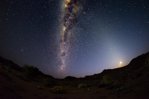 Ciel étoilé et voûte de la voie lactée avec lune montante, capturée dans le désert du namib en namibie, afrique. Photo Premium