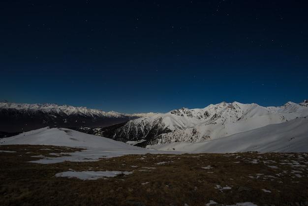 Ciel étoilé vue de nuit sur les alpes. chaîne de montagnes enneigée au clair de lune. Photo Premium