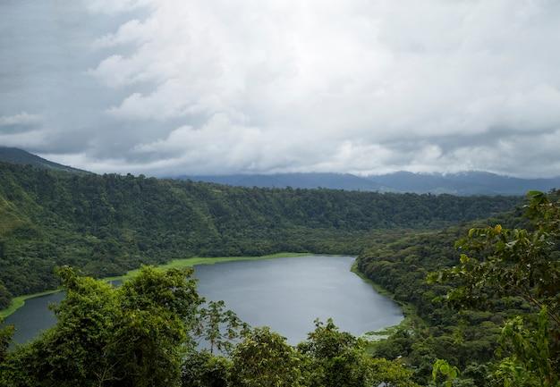 Ciel nuageux sur la belle forêt tropicale et le lac Photo gratuit