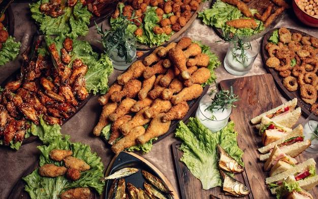 Ciel de pépites avec cuisses de poulet, boulettes de poulet au poulet, rondelles d'oignon, ailes de poulet marinées Photo gratuit