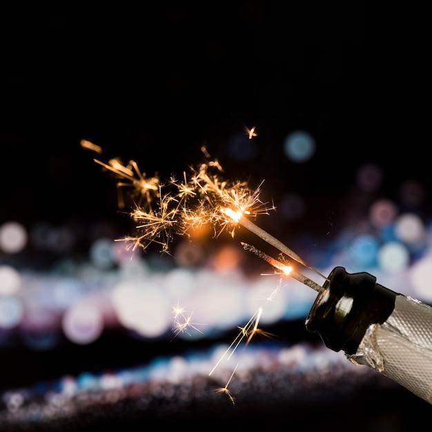 Cierge magique de feu dans une bouteille de champagne sur fond de bokeh dans la nuit Photo gratuit