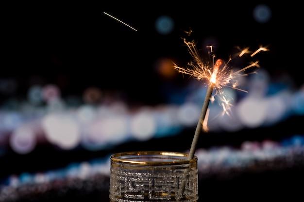 Cierge magique de noël sur fond sombre avec des lumières de bokeh Photo gratuit