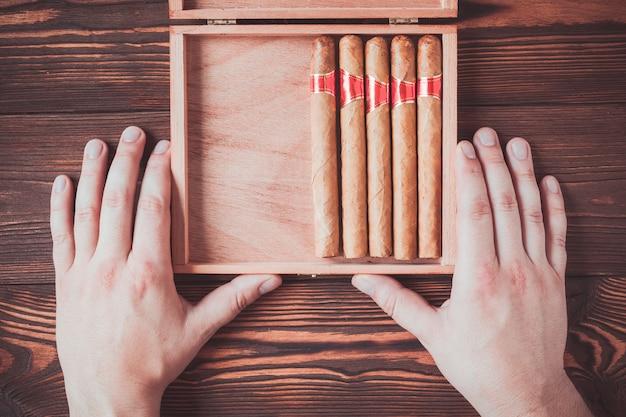 Cigares cubains dans une boîte dans des mains mâles sur un fond en bois Photo Premium