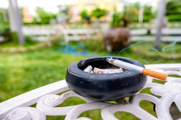 Cigarette allumée avec de la fumée sur un cendrier en céramique Photo Premium