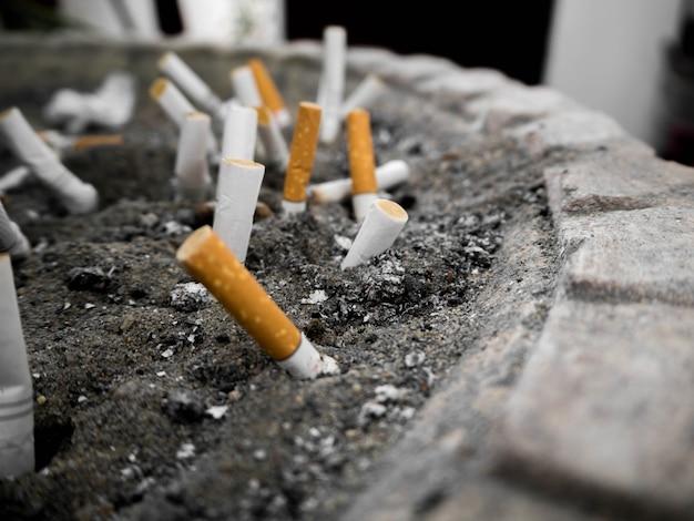 Cigarette bout à bout dans le pot. beaucoup de talon de cigarette dans le cendrier de sable. Photo Premium