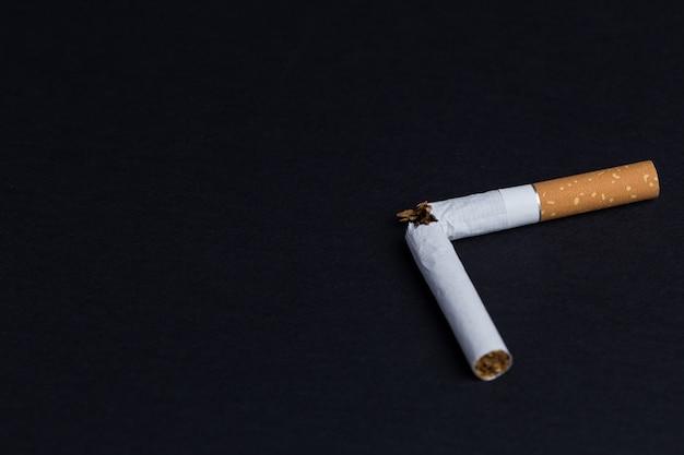 Cigarette brisée sur fond noir Photo Premium