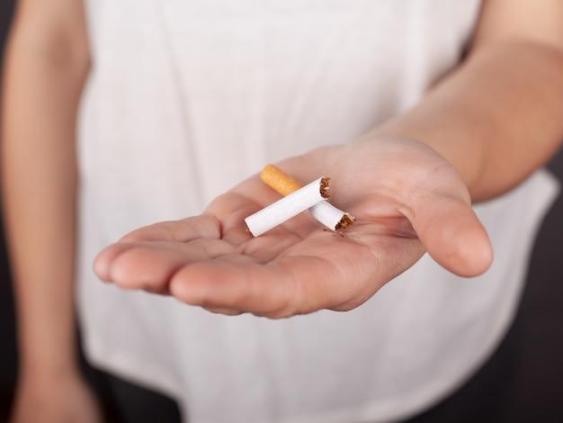 Cigarette Cassée Dans Une Main Féminine, Arrêtez De Fumer, Dépendance à La Nicotine. Photo Premium