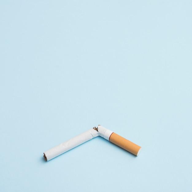 Cigarette cassée unique sur fond bleu Photo gratuit