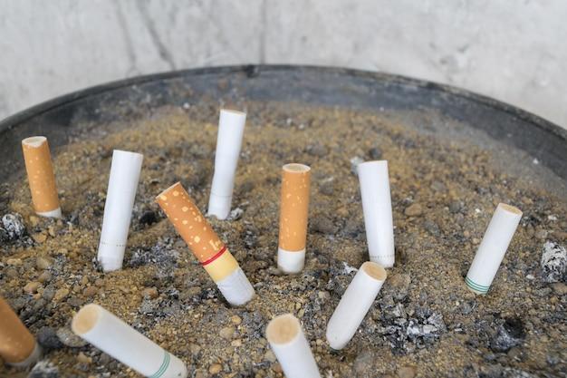 Cigarette dans un cendrier extérieur avec du sable closeup Photo Premium
