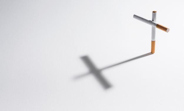 Une cigarette avec son ombre faisant une croix Photo gratuit