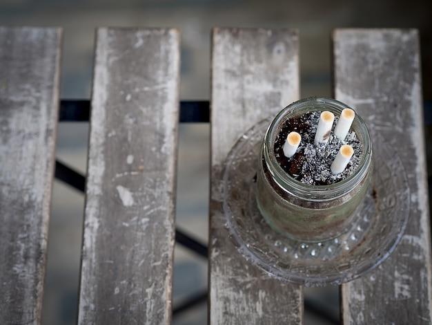 Cigarettes Et Déchets Dans Le Cendrier Sur La Table En Bois, Sale Et Fumée, Dans La Zone Fumeurs Photo Premium