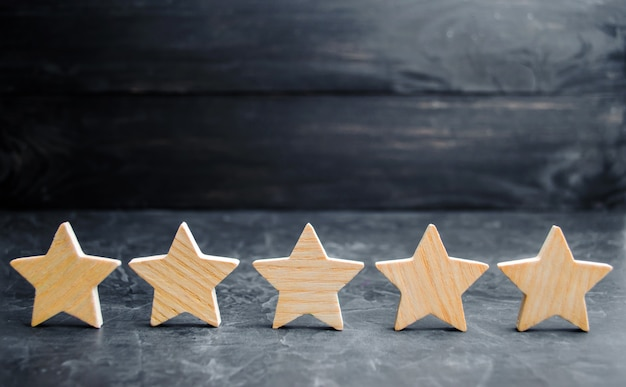 Cinq étoiles en bois. obtenez la cinquième étoile. Photo Premium