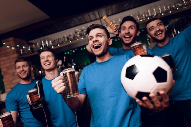 Cinq fans de football buvant de la bière et fêtant au bar Photo Premium