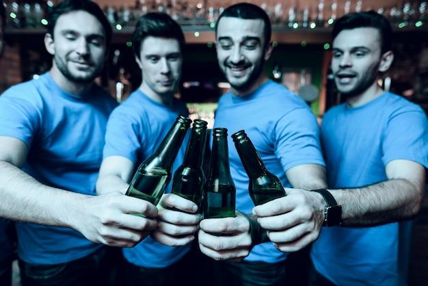 Cinq fans de sport buvant de la bière et fêtant. Photo Premium