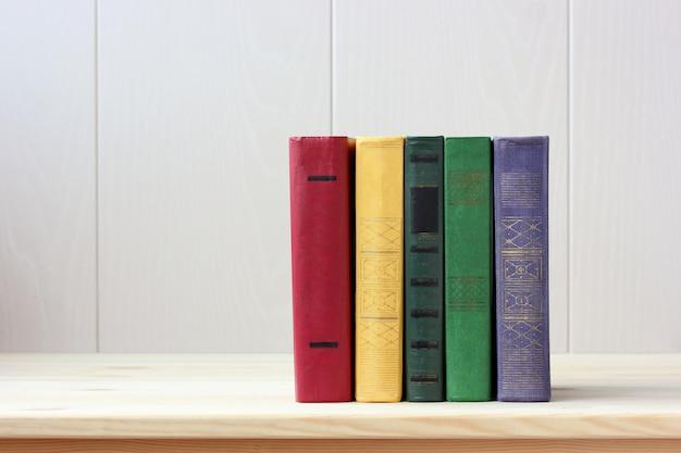 Cinq livres aux couvertures dures colorées sur la table. Photo Premium