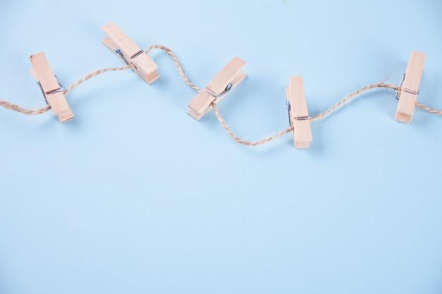 Cinq pinces à linge en bois sur une corde sur fond bleu Photo Premium
