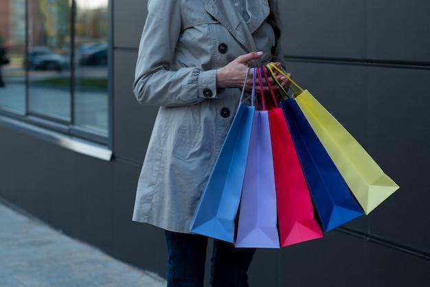 Cinq sacs colorés pour faire des emplettes dans une main féminine. Photo Premium