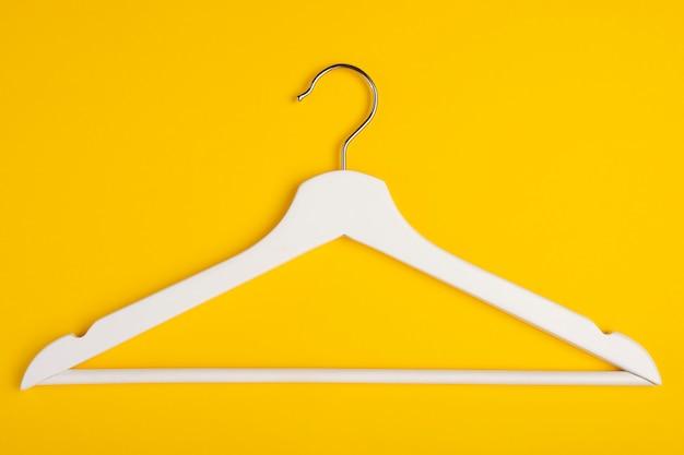 Un cintre en bois isolé sur jaune. Photo Premium