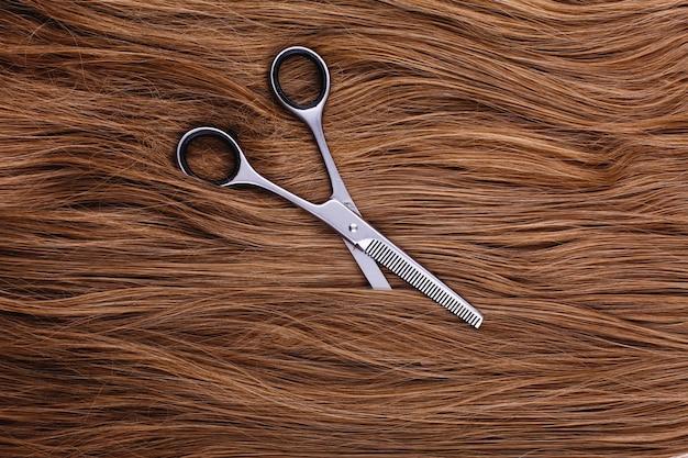 Des ciseaux en acier reposent sur la vague des cheveux bruns soyeux Photo gratuit