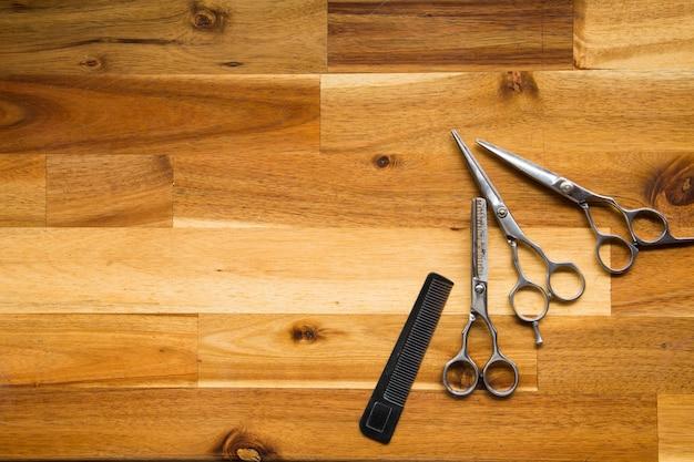Ciseaux de coiffeur professionnels élégants sur fond de bois, coupe de cheveux et ciseaux à amincir Photo Premium
