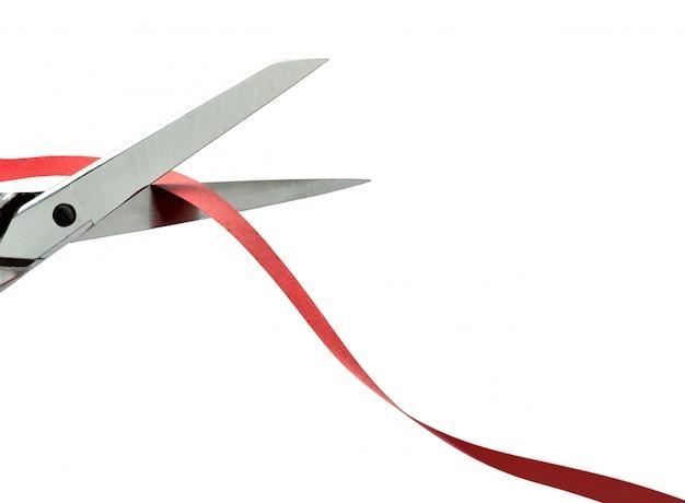 Ciseaux coupant un ruban rouge. un tracé de détourage Photo Premium