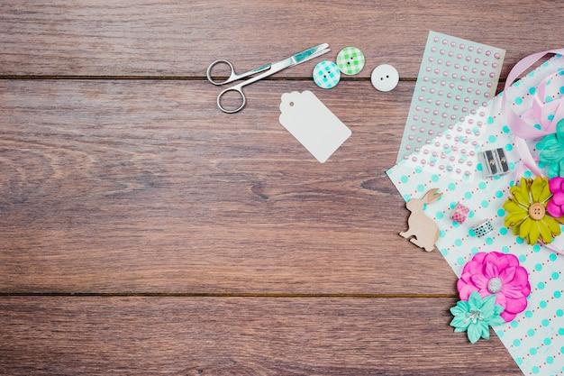 Ciseaux; étiquette; boutons; autocollant de perles et de fleurs sur papier sur le fond en bois Photo gratuit