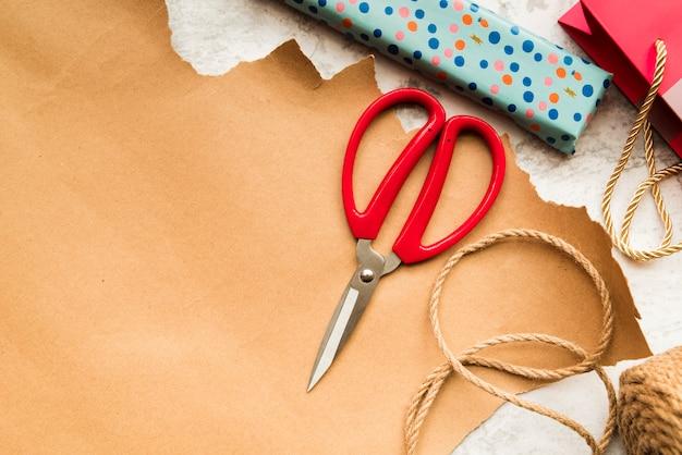Ciseaux; ficelle de jute et boîte-cadeau enveloppée sur du papier brun Photo gratuit