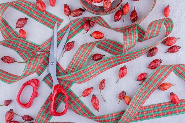 Ciseaux, Rubans De Couleur Bonbon De Noël Et Fruits Rose Sur Fond Blanc. Photo gratuit