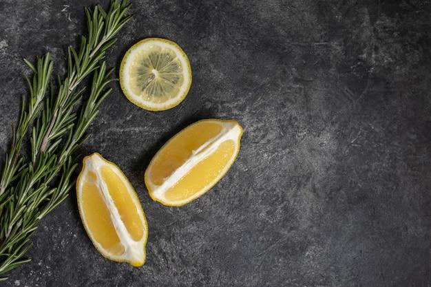 Citron frais et romarin sur un fond de texture sombre Photo Premium
