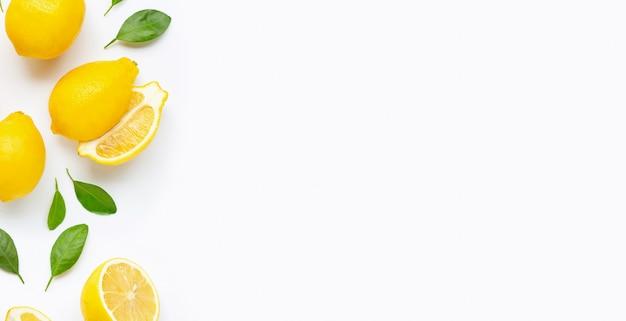 Citron frais et des tranches avec des feuilles isolés sur blanc. Photo Premium