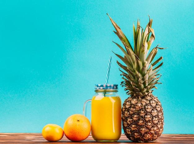 Citron; orange; ananas et jus bocal avec de la paille sur fond turquoise Photo gratuit