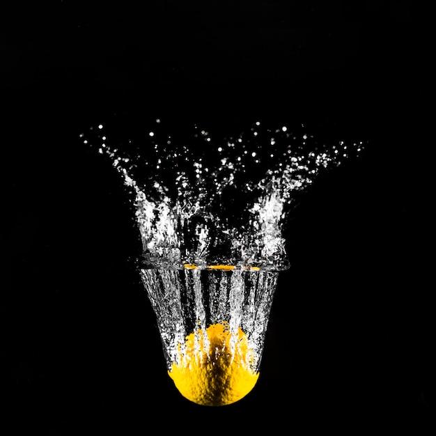 Citron plongeant dans l'eau Photo gratuit