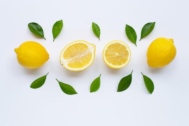 Citron et des tranches avec des feuilles isolés sur blanc. Photo Premium
