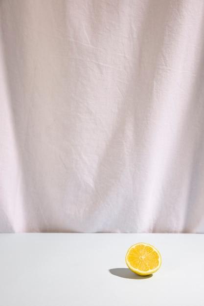 Citron vert coupé en deux sur un bureau blanc Photo gratuit