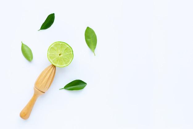 Citron vert frais avec presse-agrumes en bois blanc Photo Premium