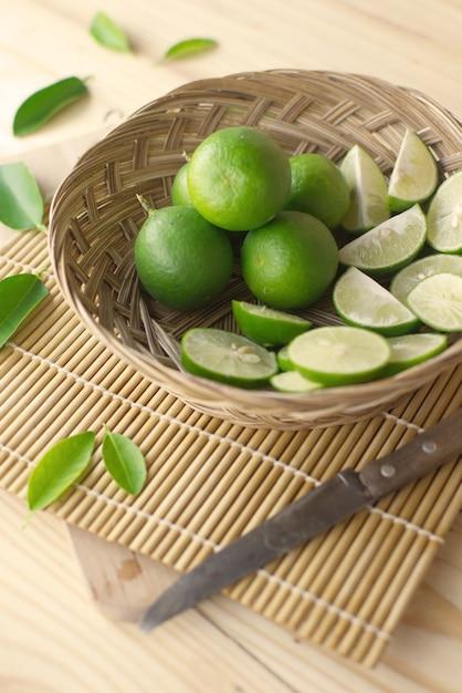 Citron vert avec tranche de citron vert dans un panier en bambou avec couteau et feuilles. Photo Premium