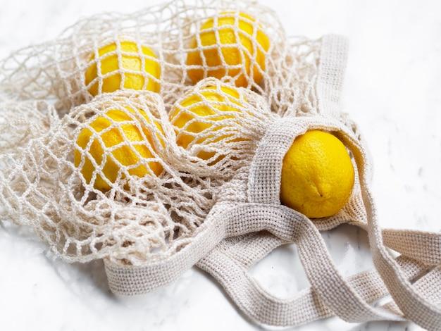 Citrons à angle élevé dans un sac en filet de coton Photo gratuit