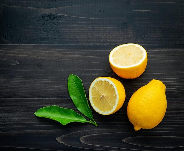 Citrons frais et citrons feuilles sur un fond en bois sombre. Photo Premium