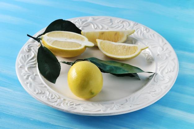 Citrons jaunes frais avec des feuilles sur une assiette sur fond bleu Photo Premium