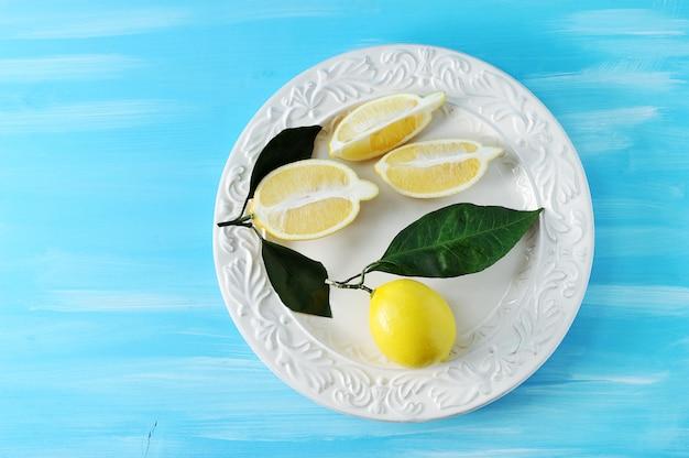 Citrons jaunes frais avec des feuilles sur une assiette sur un fond en bois bleu Photo Premium