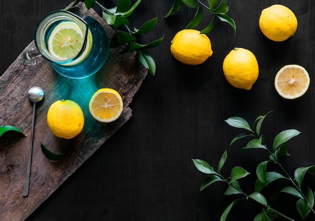 Citrons jaunes frais sur fond noir Photo Premium