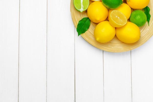 Citrons et limes sur un fond en bois. Photo Premium