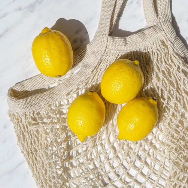 Citrons plats poser sur un sac en crochet Photo gratuit