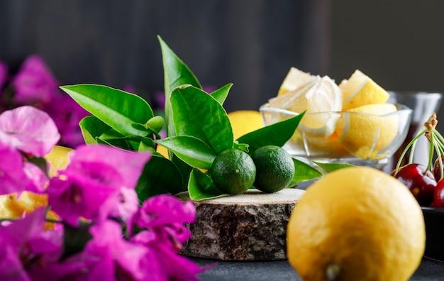 Citrons Avec Tranches, Fleurs, Planche De Bois, Gros Plan De Cerises Sur Une Surface Grise Photo gratuit