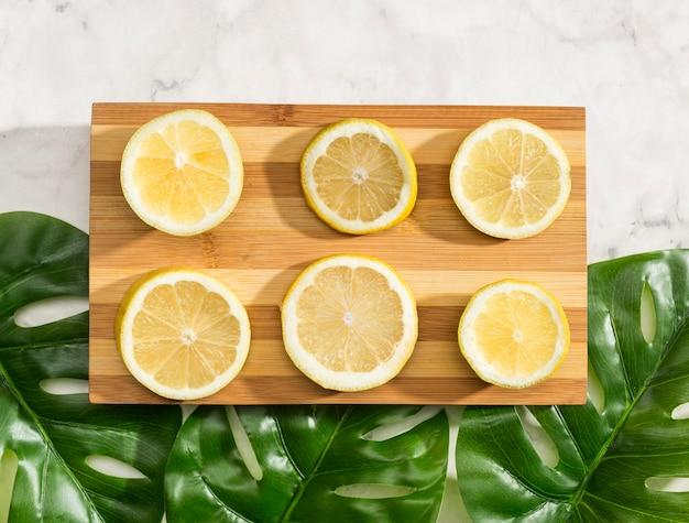 Citrons en tranches vue de dessus sur planche de bois Photo gratuit