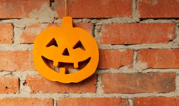 Citrouille d'halloween se bouchent sur le fond de mur de brique Photo Premium
