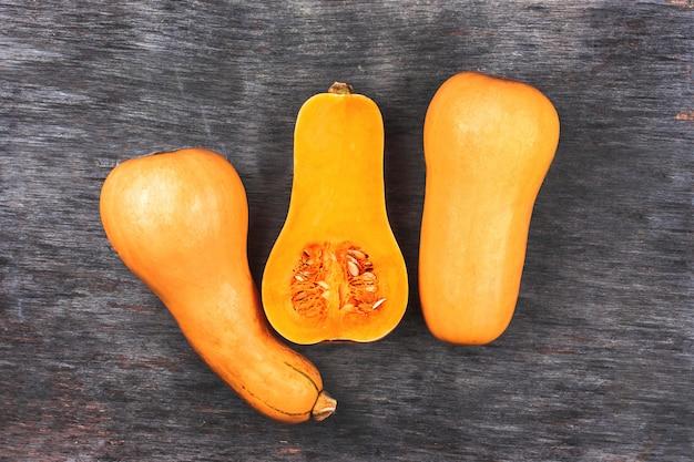 Citrouille sur une table en bois noire. trois citrouilles orange en forme de poire douce. demi citrouille coupée au milieu Photo Premium